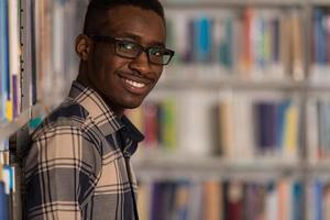 estudante do sexo masculino feliz com livro na biblioteca foto