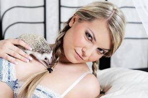 jovem camponesa brincando com o ouriço na cama foto