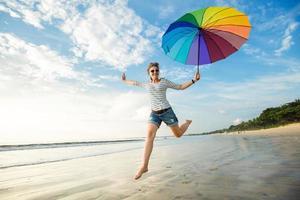 jovem alegre com guarda-chuva de arco-íris se divertindo na foto