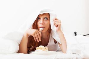 menina ruiva comendo biscoito na cama foto