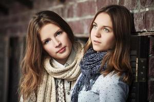 meninas contra uma parede de tijolos