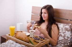 bela jovem tomando café da manhã na cama pela manhã foto