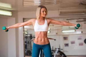 garota engajada em exercícios físicos com halteres foto