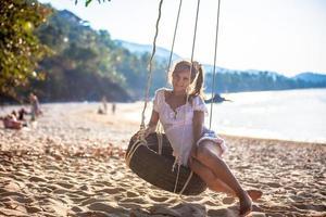 mulher sentada no balanço da praia paradisíaca foto