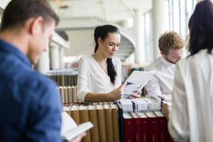 grupo de estudantes estudando na biblioteca foto