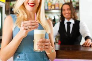 barista com cliente em seu café ou coffeeshop foto