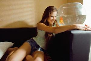 linda mulher brincando com peixinho dourado em casa, luz do sol pela manhã foto