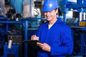 trabalhador de fábrica escrevendo relatório foto