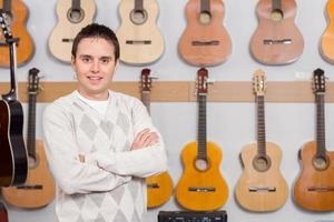 retrato de um jovem proprietário em uma pequena loja de música foto