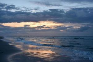 ondas batendo na praia durante o pôr do sol foto