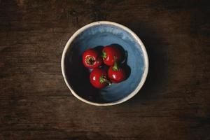 cerejas vermelhas em uma tigela na mesa de madeira foto
