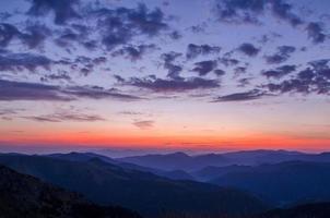 silhueta da montanha contra o pôr do sol colorido e o céu nublado
