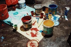 latas de tinta, pincéis e telas