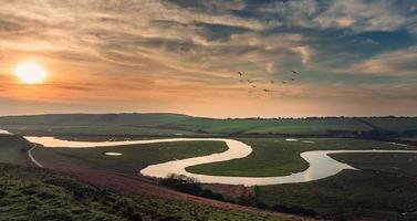 riacho sinuoso através do campo gramado ao pôr do sol