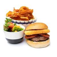 hambúrguer com recheios e batatas fritas no fundo branco foto