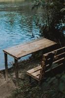 mesa de madeira perto do lago foto