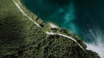 vista aérea da estrada por água e floresta verde foto