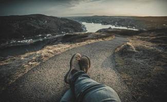 pessoa sentada na formação rochosa marrom perto da água foto