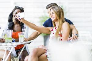 grupo de amigos sentados em uma mesa tirando selfies