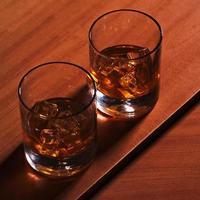 copo de uísque alto com gelo em fundo de madeira.