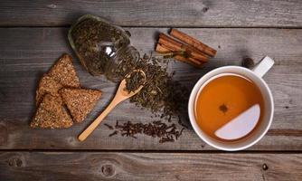xícara de chá verde, biscoitos e canela em fundo de madeira foto