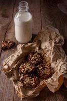 biscoitos caseiros de aveia com nozes e garrafa de leite foto