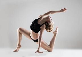 bela jovem de camiseta preta e shorts dançando foto