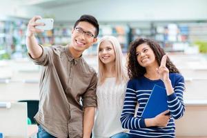 menino asiático, menina loira e mulher afro-americana fazendo selfie