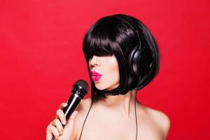 menina elegante cantando com um microfone, fundo vermelho. karaokê foto