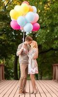 casal com balões coloridos se beijando no parque