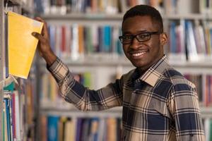 belo jovem estudante em uma biblioteca foto