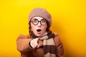 cachecol de menina ruiva e casaco em fundo amarelo. foto