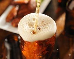despejando cerveja em copo com espuma foto