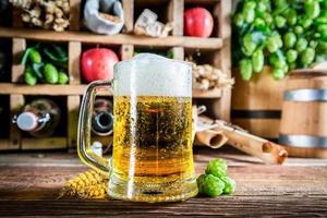 cerveja fresca e ingredientes em caixa de madeira foto