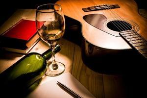 guitarra com livro vermelho e vinho em uma mesa de madeira.