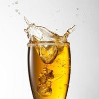 respingo de cerveja em copo isolado no branco foto