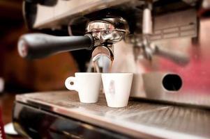 máquina de café expresso servindo café em xícaras foto