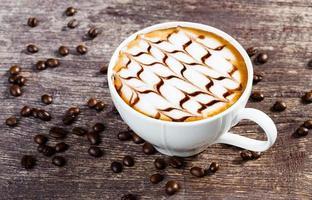 xícara de café e grão torrado na velha mesa de madeira foto