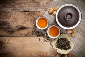 xícaras de chá com gaiwan na velha mesa de madeira foto