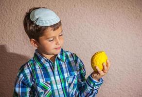 menino muito bonito segurando frutas cítricas foto