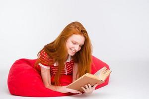 bela mulher sorridente deitada no saco de feijão e lendo um livro foto