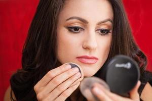 empresária com espelho de maquiagem