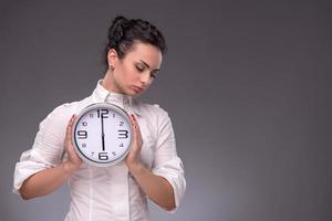 retrato de boa moça segurando o grande relógio nas mãos foto
