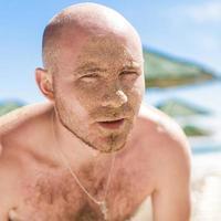 meio rosto de um homem bonito coberto de areia foto