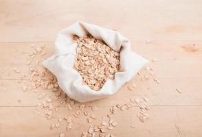 flocos de espelta em um saco de tecido creme em madeira foto