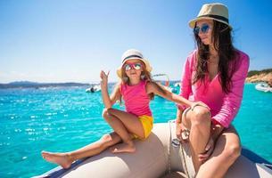 linda garota e mãe feliz durante as férias no barco foto