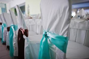 fitas turquesa na cadeira do casamento foto