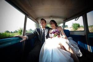 recém-casados no carro do casamento foto