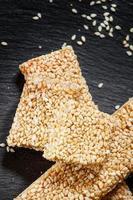barra de sementes de gergelim no mel e grãos espalhados foto