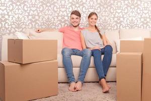 jovem casal sentado no sofá foto